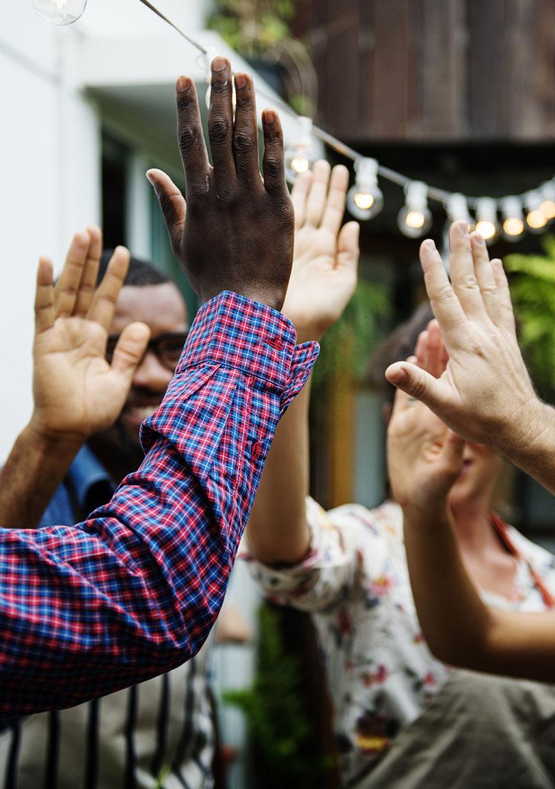 several hands do group hi five